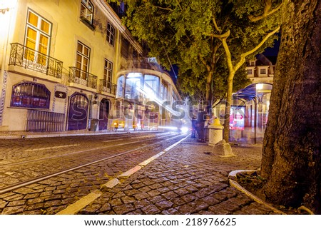 LISBON, PORTUGAL - September 13, 2014: Traditional yellow tram downtown Lisbon by night on September 13. Trams are used by everyone and also keep traditional style of the historic center of Lisbon.
