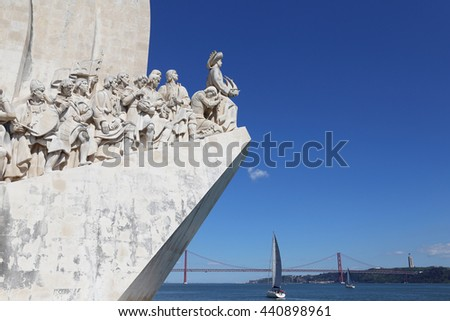 Lisbon's Discoveries monument showing Henry the Navigator gazing our over the River Tagus with small sailing boats and the 24 April bridge behind. - stock photo