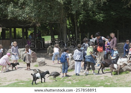 LISIEUX, FRANCE - JUNE 29, 2011: Group of children and adults in petting zoo of Zoo de Cerza in Lisieux, France. A woman and some children are afraid of the naughty and intrusive goats.  - stock photo