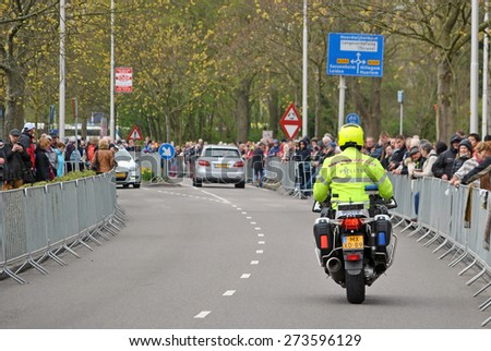 "LISSE, THE NETHERLANDS, 25 APRIL 2015 - Police officer on a motor cycle during the annual Dutch flower parade ""Bloemencorso"". - stock photo"