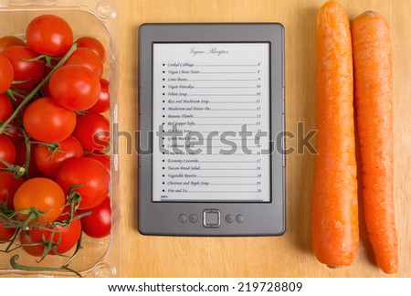 List of Recipes on a Tablet among Tomatoes and Carrots - stock photo