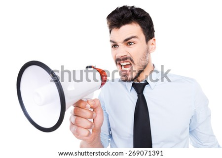 Listen to me! Furious young man in shirt and tie holding megaphone and shouting while standing against white background - stock photo