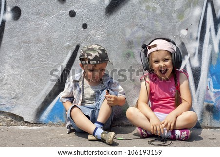 listen to music abstract concept with singing children against graffiti wall - stock photo