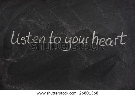listen to your heart phrase handwritten with white chalk on a blackboard with eraser smudge patterns