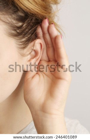 Listening gossiping, Close-up of female ear and palm behind  - stock photo