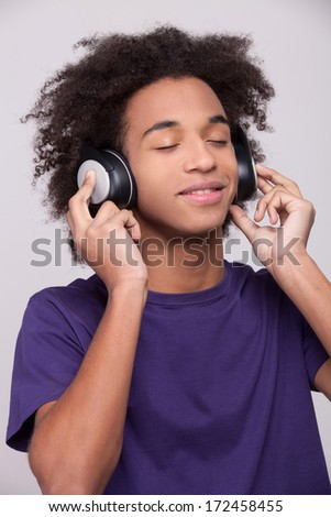 Listening to his favorite music. Cheerful African teenager in headphones listening to the music and grimacing while standing isolated on grey background - stock photo