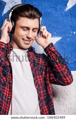 Listening to his favorite music. Cheerful young man in checked shirt keeping eyes closed and adjusting his headphones  while standing against background - stock photo