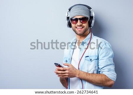 Listening to his favorite song. Handsome young stylish man in headphones holding MP3 Player and smiling while standing against grey background - stock photo