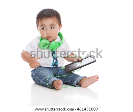 Listening to music.  Adorable biracial baby with a tablet and headphones.  Isolated on white.