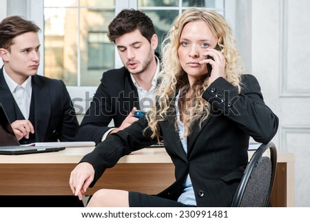 Listening to the client. Businesswoman listening to the client on a mobile phone while his colleague businessmen talking in the background sitting at table - stock photo