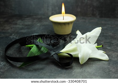 lit a candle with a flower tied with black ribbon  - stock photo