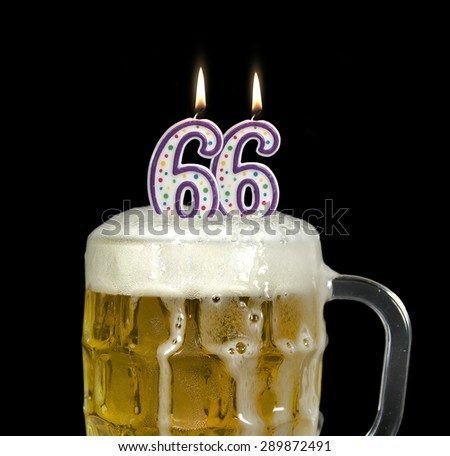 lit birthday candles for 66th birthday in a mug of beer isolated on black - stock photo