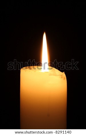 Lit candle on black background - stock photo