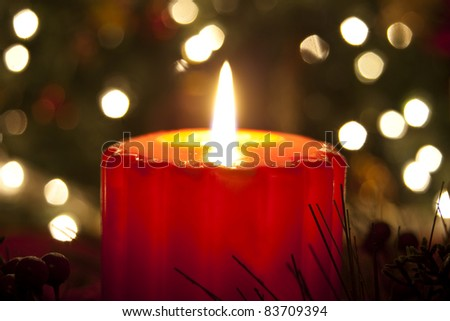 Lit candle on Christmas Eve in front of the diffused lights on a Christmas tree - stock photo