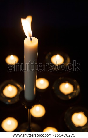 Lit candles and tealights on a dark background.