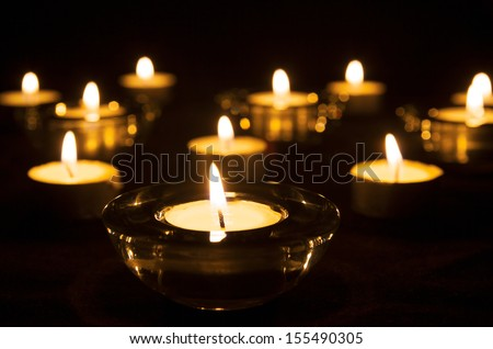 Lit candles and tealights on a dark background. - stock photo