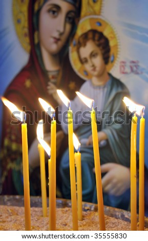 Lit candles in a Christian Orthodox church, with an an icon of Virgin Mary and Jesus in the background