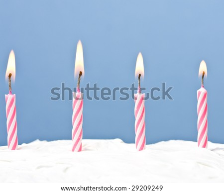 lit candles on a white frosted cake blue background - stock photo