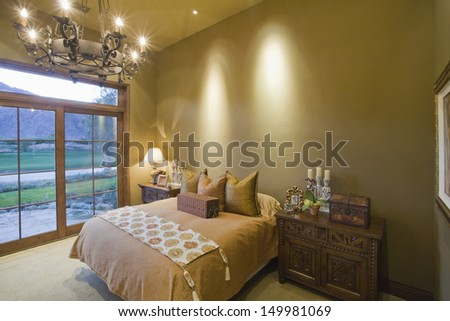 Lit chandelier over bed with view of landscape through window at home - stock photo