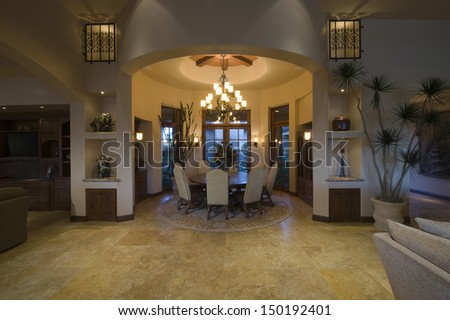 Lit chandelier over circular dining room of a spacious and modern home - stock photo