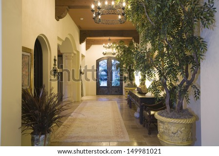 Lit chandeliers at entrance hallway along potted plants in modern house - stock photo
