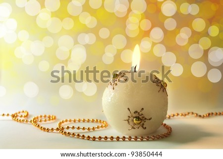 Lit christmas candle on a golden background - stock photo