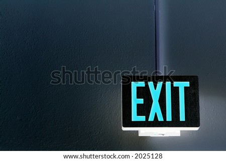 lit exit sign hanging from the ceiling - stock photo