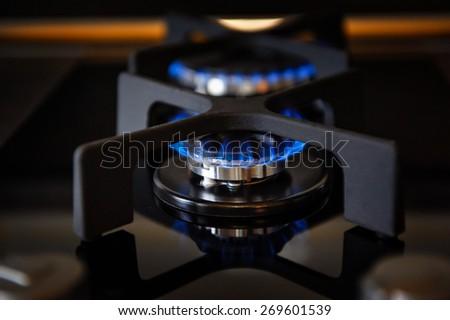 Lit gas burner blue fire on a glass plate closeup - stock photo