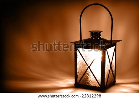 Lit lantern on dark background, sepia toned - stock photo