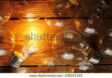 lit light bulb among unlit ones on wood - stock photo