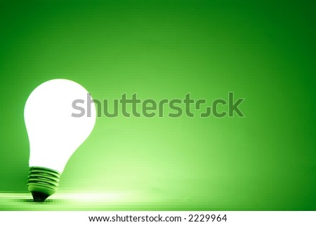 Lit light bulb with a tiled green background