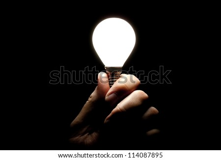 Lit lightbulb held in hand on black background - stock photo
