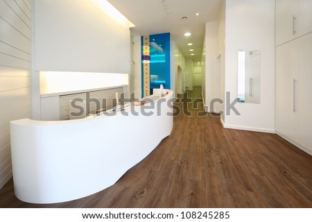 Lit reception area in dental clinic. Empty workplace with table with computer. - stock photo
