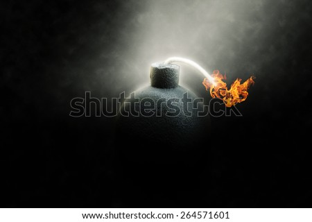 Lit round black bomb with a burning fuse counting down to detonation illuminated in a shaft light shining through the darkness, conceptual image - stock photo