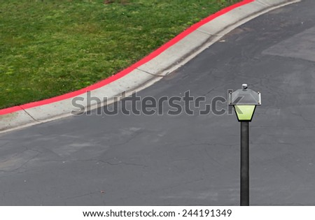 Lit street lamp in early morning. Overhead view. Grass and red zone. Blurred background. Room for text, copy space.  - stock photo