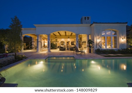 Lit swimming pool and building exterior at night - stock photo