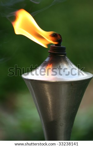 Lit torch with orange flame in garden used as mosquito repellent - stock photo