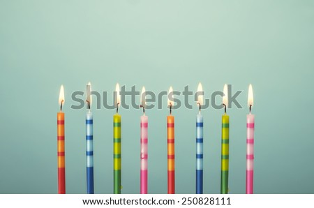 Lit up celebration candles in various color and stripes