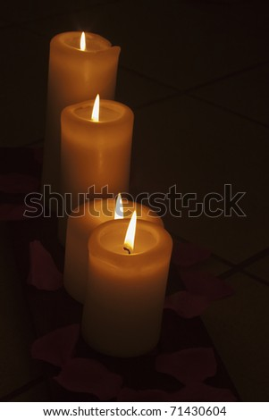 Lite white candles coming out of darkness