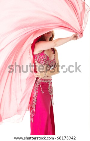 Lithe adult caucasian belly dancer with red hair and pink belly dancing outfit performing a dance with veils on a white background. Not Isolated - stock photo