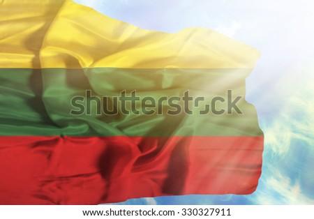 Lithuania waving flag against blue sky with sunrays - stock photo