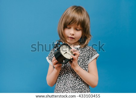 litle girl with a clock, alarm clock - stock photo