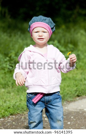 litlle girl on walk holding a flower - stock photo