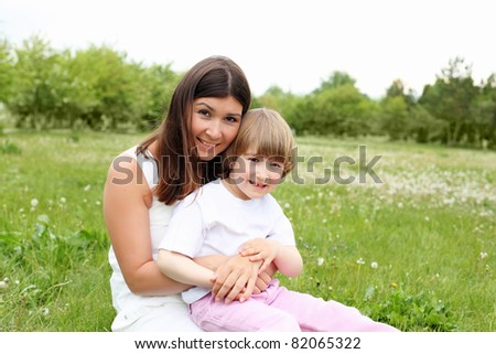litlle girl with her mother outdoors on the grass
