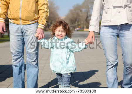 litlle girl with parents in spring park