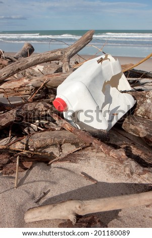 litter amongst driftwood on a sandy beach  - stock photo