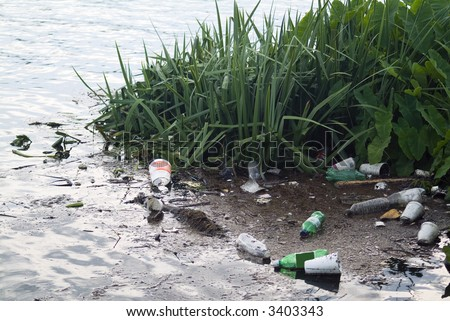 Litter from runoff after a big rainstorm polluting the river. - stock photo