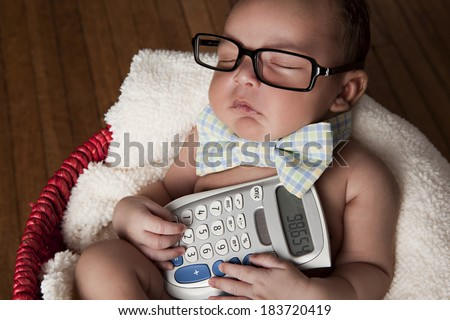 Little Accountant.  Adorable newborn wearing glasses and a bow-tie and holding a calculator. - stock photo