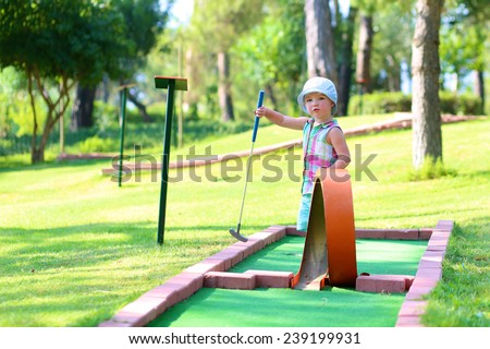 Little active child, two cute toddler girl, playing miniature golf enjoying sunny summer vacation day outdoors in the park - stock photo