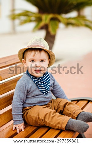 Little adorable baby boy in a straw hat and brown pants sitting on the bench amid palm trees and smiling, summer - stock photo